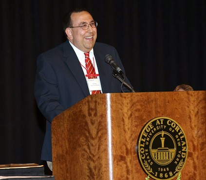 Elia serving as emcee at the podium of a 2014 SUNY Cortland event.